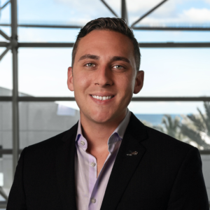 Real estate agent Joshua Zorn in front of window overlooking beach in southern Florida