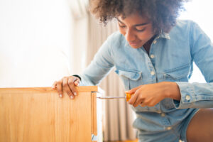 Portrait of young afro woman repairing furniture with a screwdriver at home. Repair and renovation home concept.
