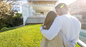 Young Couple standing in front of a modern new house. They are looking at the luxury home with their backs to the camera. They are sanding on a lawn and embracing.