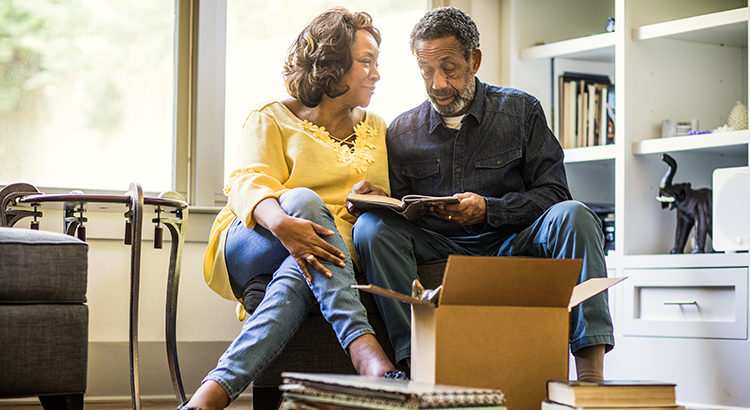 Senior couple packing books to move