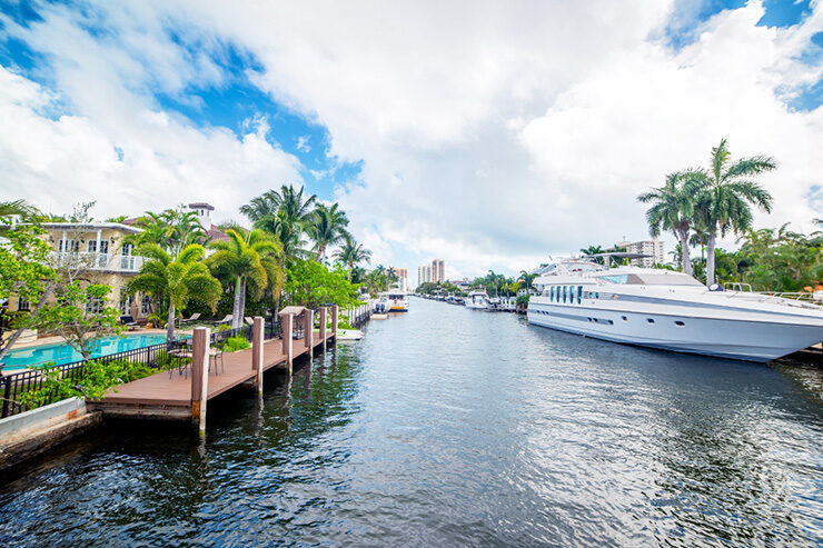 Yacht and boats lined along community waterway with dock seating and palm trees