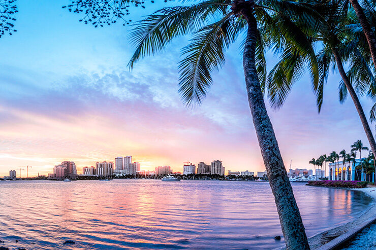 Florida beach at sunset with city and boats in background and palm trees